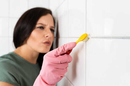 Woman Cleaning Grout with Toothbrush